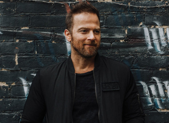 Kip Moore against dark brick wall