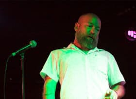 Kyle Kinane in front of microphone looking down