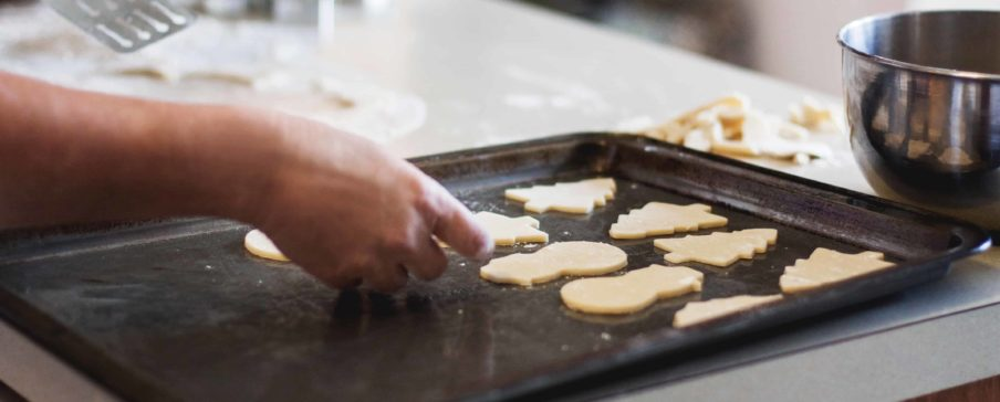 Person putting sugar cookies on a baking sheet. Photo by Kari Shea on Unsplash