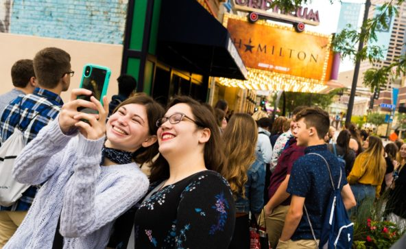 Students pose in front of the Orpheum Theatre marquee before Hamilton