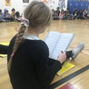 A girl reading a script while sitting on a gym floor